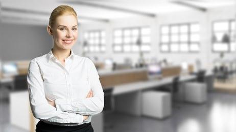junge Geschftsfrau vor Bro-Hintergrund mit vielen Computer-Arbeitspltzen